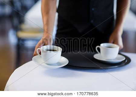 Mid section of waitress serving cup of coffee in restaurant