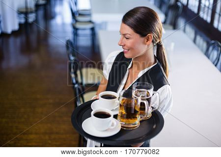 Smiling waitress holding serving tray with coffee cup and pint of beer in restaurant