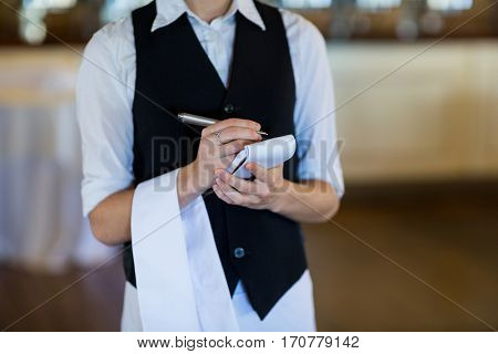 Mid section of waitress taking order in restaurant