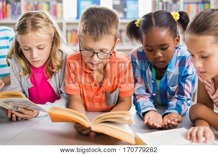 Kids reading a book in library at school