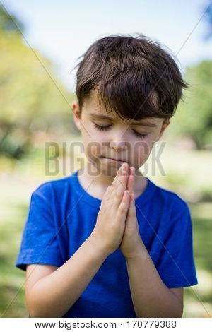 Boy praying with eyes closed in park