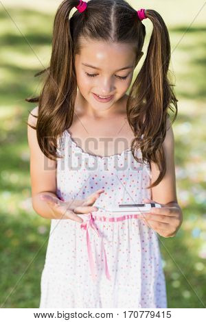 Cute girl testing diabetes on glucose meter in park