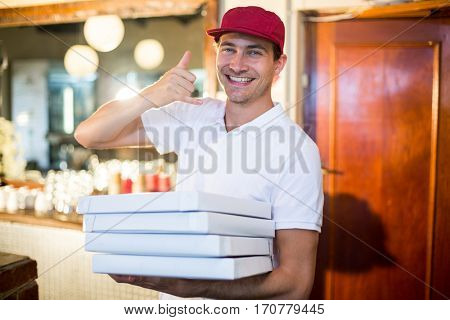 Pizza delivery man holding pizza boxes making a phone gesture in restaurant