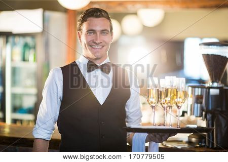 Portrait of waiter holding serving tray with champagne flutes in restaurant
