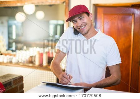 Pizza delivery man taking an order over the phone at counter in restaurant