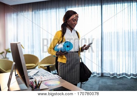 Businesswoman with yoga mat in the office