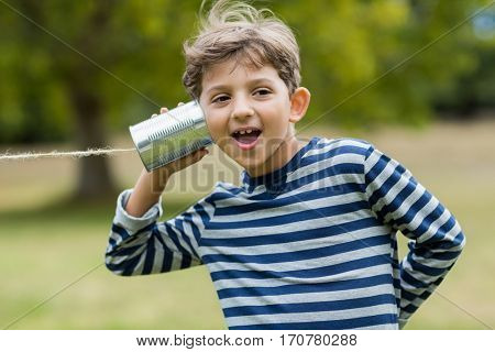 Cute boy listening through tin can phone in park