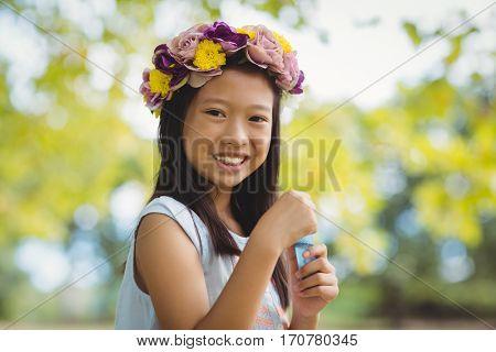 Portrait of girl wearing flower wreath holding bubble wand in park