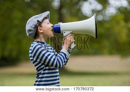 Boy speaking on megaphone in park