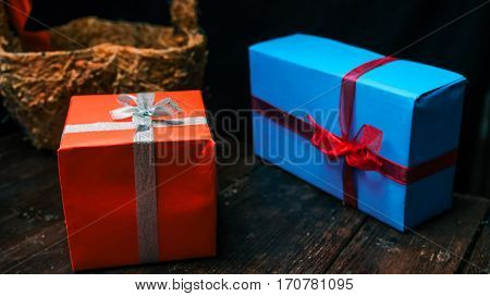 Red and blue gift boxes on dark desk. Close-up wide angle view