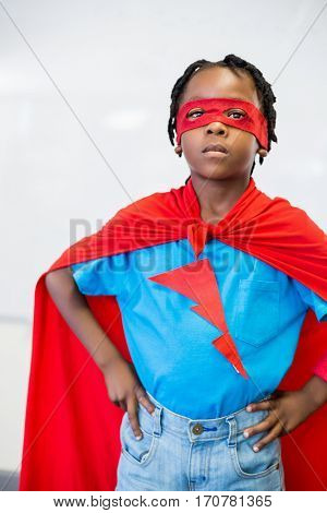 Portrait of boy standing with hand on hip pretending to be a superhero