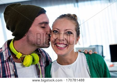 Man worker kissing his colleague in a office
