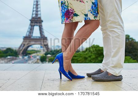 Romantic French couple having a date near the Eiffel tower. Closeup of man and woman legs during a kiss or hug. Unrecognizable lovers in Paris. Tourists enjoying vacation in France