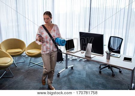 Businesswoman holding an exercise mat and looking her mobile phone in the office