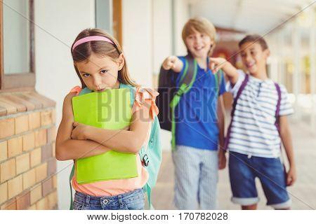 School friends bullying a sad girl in corridor at school