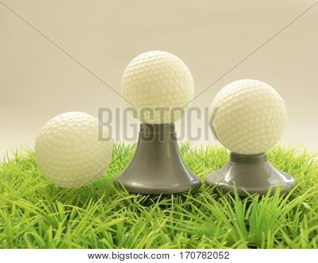 Three Golf Ball On Different Supports , Tee On Grass