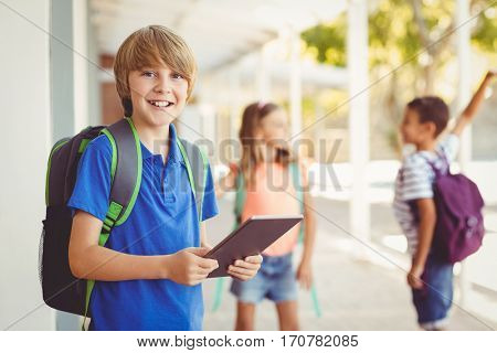 Portrait of schoolboy holding digital tablet and friends high fiving in background at school corridor