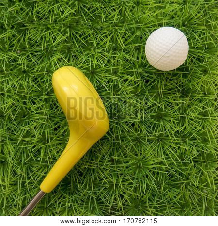 Toy A Golf Ball With A Yellow Stick On The Background Of Green Grass