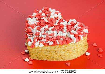 Pile of pancakes in the shape of a heart on red background with little white and red sugar hearts
