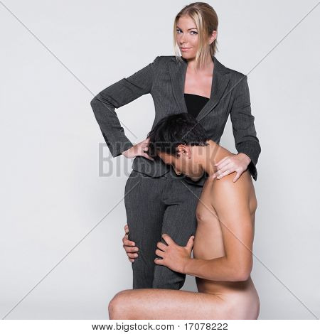 young couple with man naked kneeling in front a woman in studio on isolated grey background