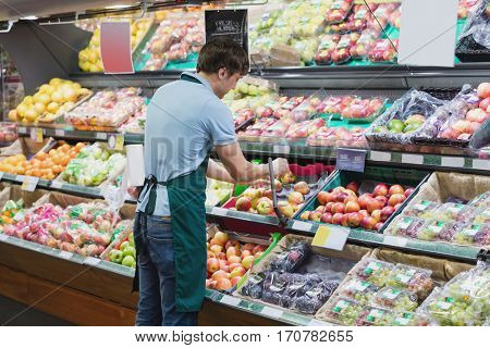 Shop assistant arranging shelves in a grocery shop