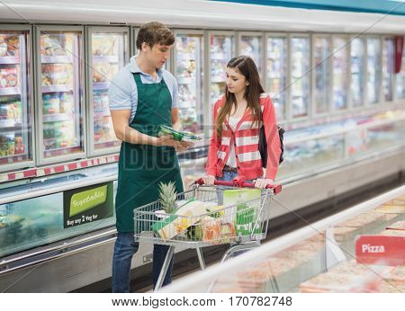 A man grocer advising his customer on a grocery
