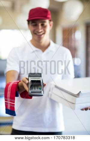 Happy pizza delivery man showing credit card machine in restaurant