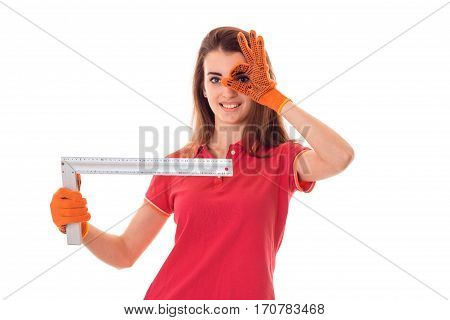 cutie young brunette lady makes renovation in gloves with tools in her hands and showing OK isolated on white