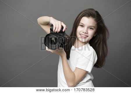 Cute brunette little girl holding an photo camera, isolated on gray background