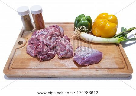 Raw meat cheek pieces of iberian pork with vegetables over wooden board. Isolated over white background