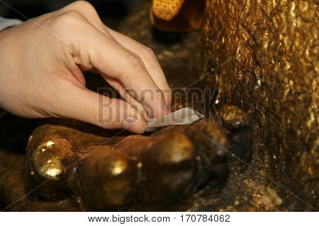Gilding Gold Leaf To Buddha For Worship. Selective Focus.