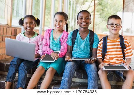 Portrait of kids using a laptop and digital tablet on stairs at school