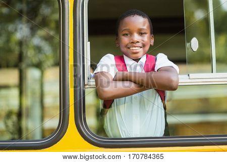 Portrait of smiling schoolboy looking from school bus