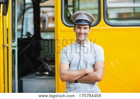 Portrait of smiling bus driver standing with arms crossed in front of bus