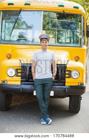 Portrait of smiling bus driver leaning with hands in pocket in front of bus