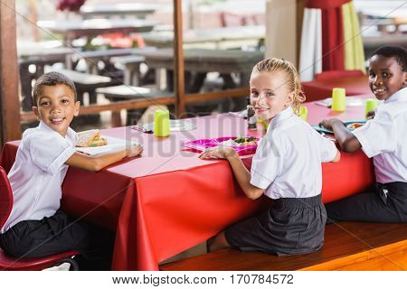 Portrait of children having lunch during break time in school cafeteria