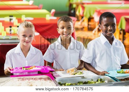 Portrait of school kids having lunch during break time in school cafeteria