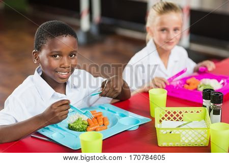 Portrait of boy and girl in school uniforms having lunch in school cafeteria