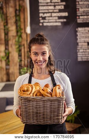 Portrait of waitress holding a basket with viennoiseries in a cafe