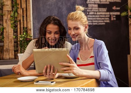 Smiling friends using a tablet in the cafe