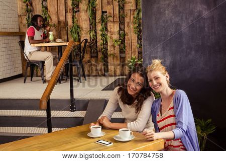 Smiling friends sitting at a table in the cafe