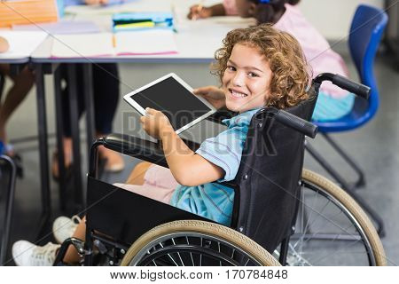 Portrait of disabled schoolboy using digital tablet in classroom at school