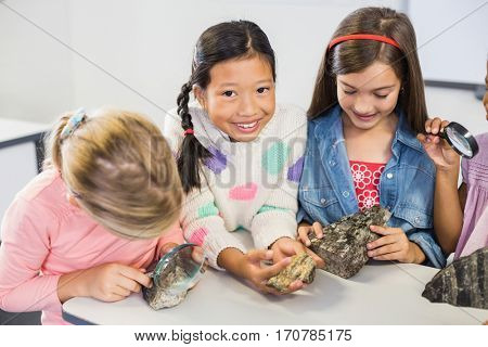 Group of kids looking at specimen stone through magnifying glass in classroom