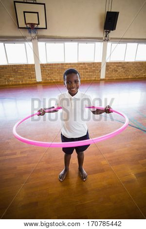 Portrait of smiling boy playing with hula hoop in school gym