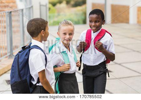 Smiling school kids standing in school terrace