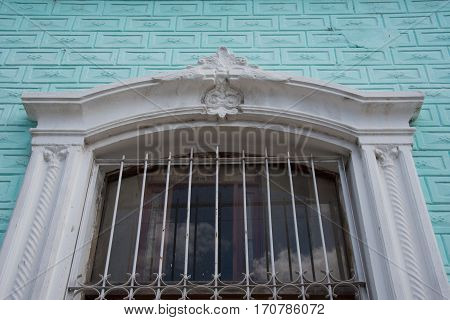 Cuban colonial architecture decorations in vintage house window. The window has iron work for protection and beauty.