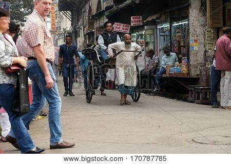 KOLKATA, INDIA - FEBRUARY 10: Traditional hand pulled indian rickshaw driver working on the street in Kolkata on February 10, 2016.