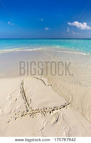 Waves wash away a heart drawn on sand of a tropical beach. Concept of romantic love, broken heart etc.