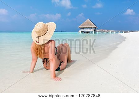 Beautiful young woman in sunhat sitting relaxed on sand, tropical beach in Maldives