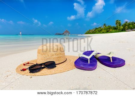 Beach accessories on sand, clear turquoise ocean in Maldives. Vacation, travel concept. Sunglasses, flip-flops and sunhat
